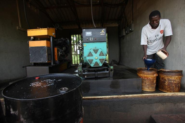 פועל בחווה בניגריה מוזג דיזל לגנרטור