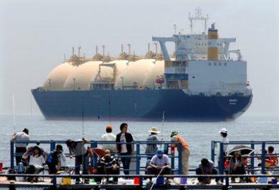 דייגים ביפן על רקע ספינת LNG