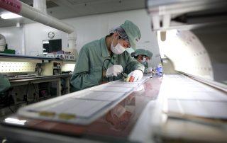 פועל במפעל ליצור פאנלים סולאריים בסין