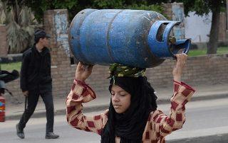 אישה מצרית נושאת בלון גז ריק