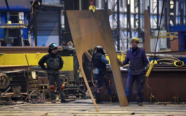 פועלים במספנה מרכיבים ספינה שתפעל על גז טבעי