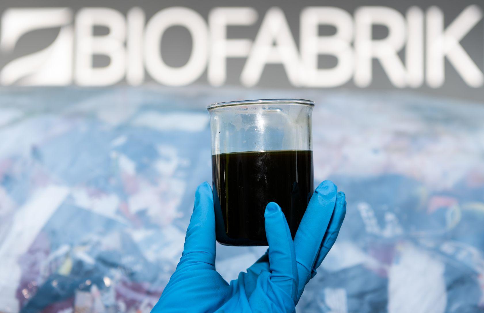 יד של פועל במפעל של ביופבריק שבבית הזיקוק וויט ריפיינרי בסקסוניה, גרמניה, מחזיק כוס של נפט ממוחזר