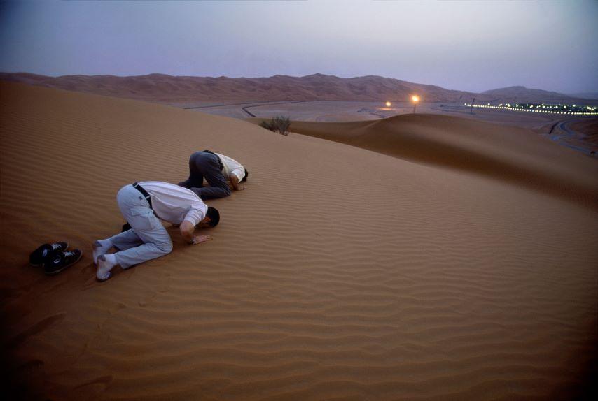 פועלים מתפללים על רקע מפעל של ערמקו במדבר